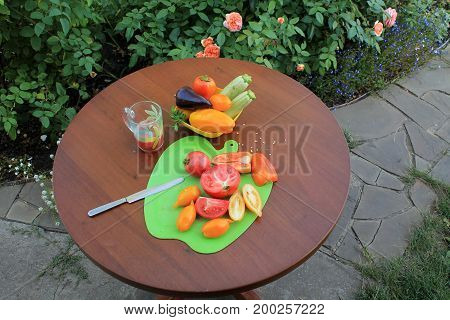 Tomatoes and peppers sliced on cutting board and glass of tomato juice оn wooden table in garden patio with flowers. Nearby there is dish with zucchini and sweet pepper.