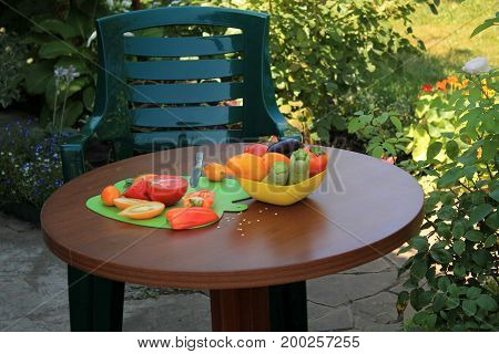 Armchair and wooden table with sliced ripe tomatoes and peppers in garden patio with flowers. Nearby there is dish with zucchini and sweet pepper.