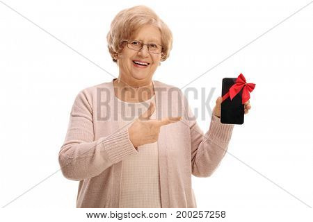 Mature woman showing a phone wrapped with red ribbon as a gift and pointing isolated on white background