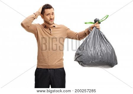 Young man with a garbage bag holding his head in disbelief isolated on white background
