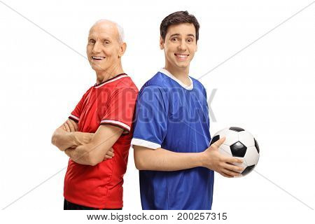 Elderly soccer player and a young player with a football looking at the camera and smiling isolated on white background