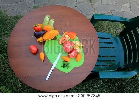 Armchair and wooden table with sliced ripe tomatoes and peppers in garden patio. Nearby there is dish with zucchini and sweet pepper. Top view.