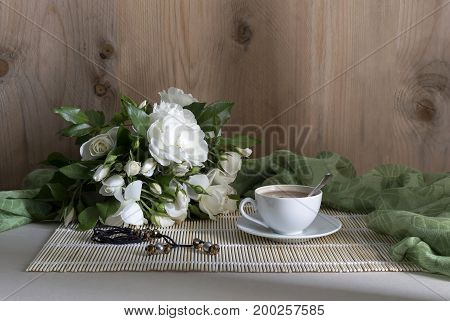 The bouquet of white roses and a cup of coffee on a table closeup