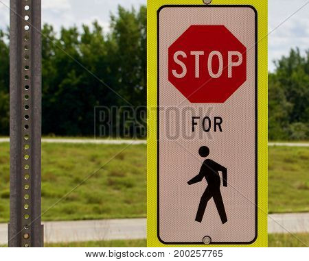 Stop for pedestrian sign against a green background
