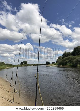 Fishing Rods Along The River Bank. A Wonderful River Landscape. A Lot Of Clouds In The Sky.