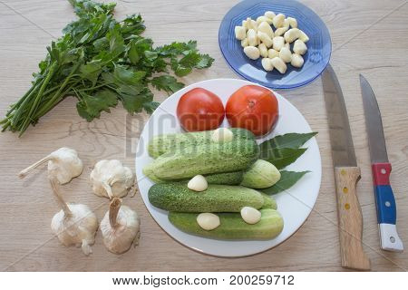 Plate with fresh vegetables on table. Green Cucumber. Fresh raw vegetables on the table