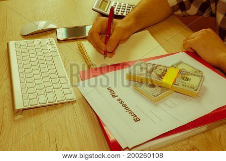 person Man pointing writing goals on a paperwriting business plan at workplace man holding pens papers notes in documents Saving money concept - Retro color