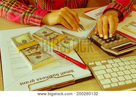 Savings finances grant economy and home concept - Female with calculator money and making notes at home. Business grant and finances concept - Retro color