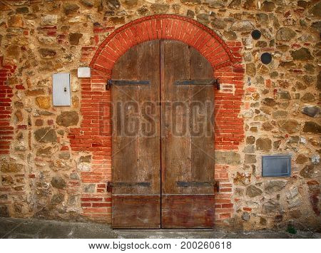 Old brown wooden door in ancient house Tuscany Italy.