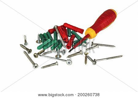Screwdriver screws and plastic dowels on a light background
