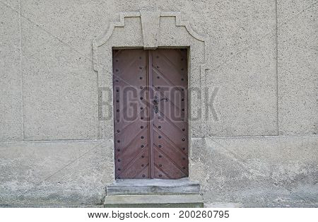 Old, wooden door. Painted with brown paint. Metallic iron fittings painted with black paint. Set in a brick wall with gray plaster.