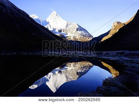 Shangri La, View Of Holy Snow-clad Mountain Jambeyang And Its Lake Reflection In Yading National Lev