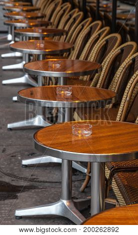 Row of tables and chairs on a traditional street terrace in Paris.