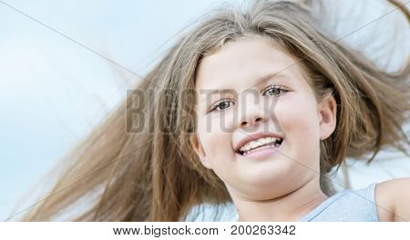 Jumping happy adorable little girl with long fluttering hair