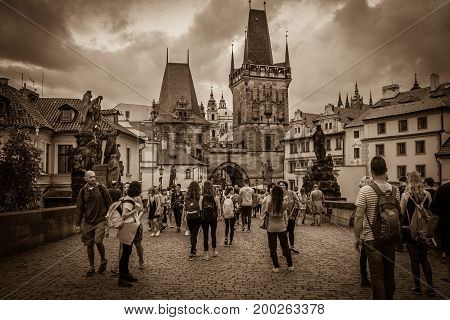 PRAGUE, CZECH REPUBLIC - AUGUST 16, 2017: Dark view of Charles Bridge (Karluv Most) and Old Town with many tourist after summer storm