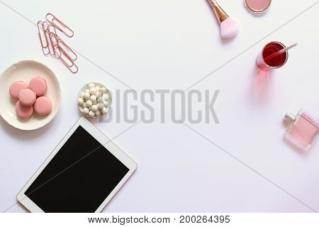 Modern styled desk top with rose gold accents, beauty products, sweets and tablet. Copy space.