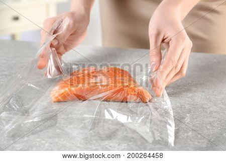 Woman preparing fresh salmon fillet in baking bag on table