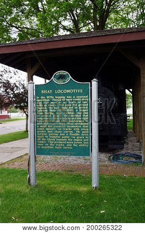 CADILLAC, MICHIGAN / UNITED STATES - MAY 31, 2017: A sign, placed by Department of State's Michigan History Division, describes the historical significance of the antique Shay locomotive on display in the Cadillac Commons City Park.