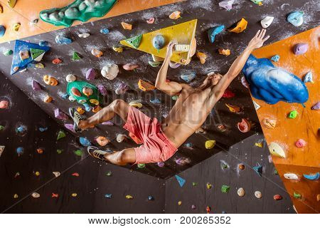 Young man bouldering in indoor climbing gym trying to reach next handhold