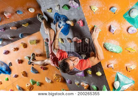Young man bouldering in indoor climbing gym trying to solver challenging problem