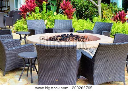 Contemporary style chairs and small tables surrounding a fire pit surrounded by lush plants and flowers taken at an outdoor patio in a residential garden