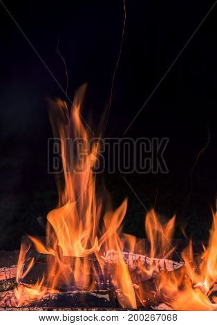 Red flame burning wood giving warmth and light on a black background