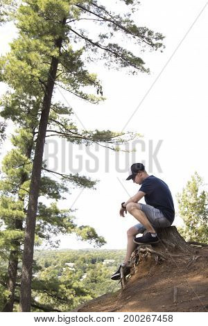 Man sitting on cliff side and looking down
