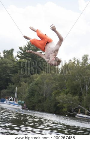Teenage boy doing a flip over the water