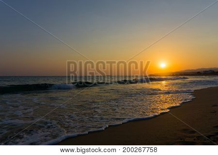 View on a beautiful warm Sunrise at the Beach. Close-up of a beautiful deserted Beach at Sunrise. Beach Background.