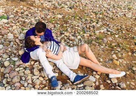 Beautiful young couple lying on stones beach