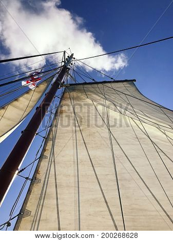 Sailing on a ketch yacht with the main and head sail up with blue sky and clouds in the background on a sunny day. Space for text.