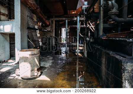 Abandoned factory building, inside the interior, workshop, pipes, water on the floor