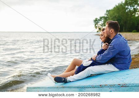 Happy loving couple embracing outdoors at summertime under blue sky.