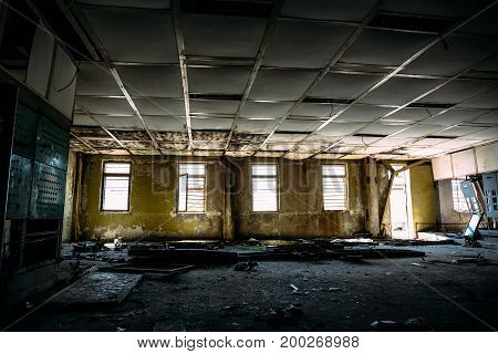 Abandoned industrial background, large ruined room with windows, control center room in abandoned factory