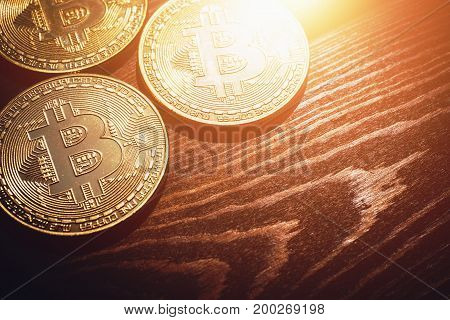 Golden Bitcoin coins - new virtual money on wooden background with light effect, toned, copy space