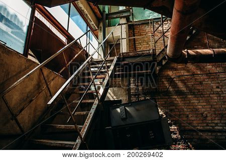 Iron rusty staircase in the brick shop of the abandoned factory, inside the interior, toned
