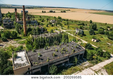 Aerial panoramic view of territory of abandoned factory, Destroyed buildings, pipes against the background of nature