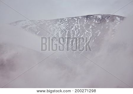 Mountains In Fog. Peaks Under Heavy Clouds.