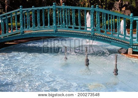 A wooden bridge over the pool with fountains in the park of the 100th anniversary of Ataturk (Alanya, Turkey).