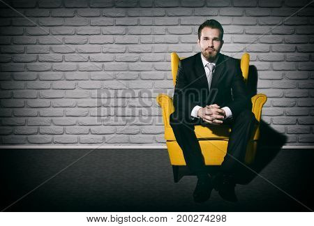 Handsome Businessman Sitting Alone On Armchair In Empty Room