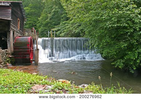 a worn red gristmill wheel next to a dam