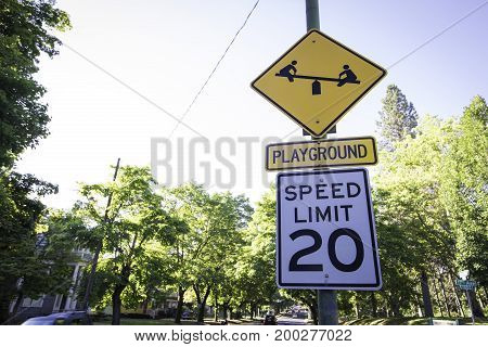 A sign cautioning to slow down for an upcoming playground
