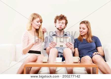 Friends browsing internet on tablet. Young people man guy and women girls relaxing at home.