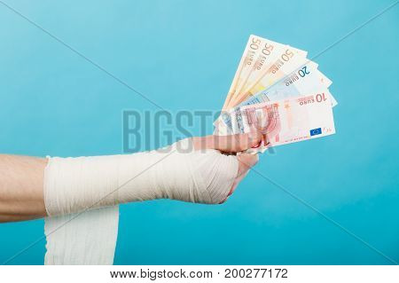 Corruption in healthcare industry. Part body male bandaged hand with money and long white bandage on blue.