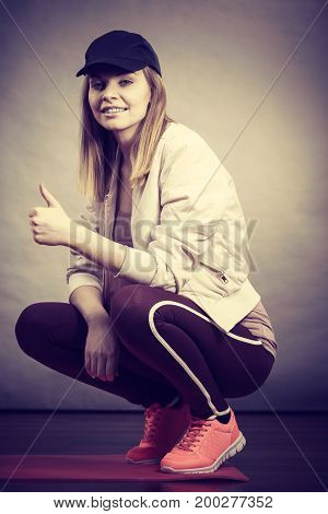 Young sporty teenage looking at camera woman wearing cap and sportswear enjoying workout results. Studio shot on grey background