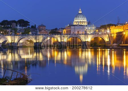 Saint Angel bridge and Saint Peter Cathedral with a mirror reflection in the Tiber River during morning blue hour in Rome, Italy.