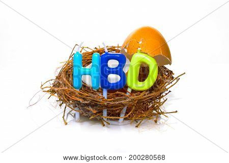 Isolated Broken Eggshell On A Nest With Candle Alphabets For Happy Birthday Concept