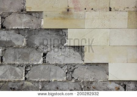 Large beige wall tiles fell off, the texture of the concrete foundation. Defective work