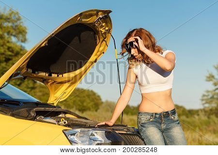 Young attractive girl opened the hood of the car and trying to sort out the damage. Trouble on the road.