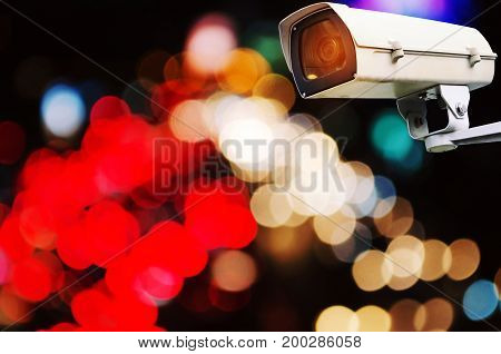 CCTV security camera system operating with abstract night light bokeh blurred view of street traffic light in the city at night surveillance security technology concept color tone effect